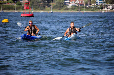 Poole, Dorset, England - June 02 2018: Two caucasian middle aged men kayaking in Poole Harbour, a busy shipping lane Sajtókép