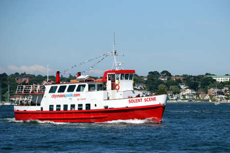 Sandbanks, Dorset, England - June 02 2018: The red and white Solent Scene pleasure cruiser sailing through Poole Harbour on its way to Swanage Sajtókép