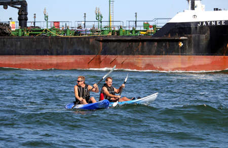 Poole, Dorset, England - June 02 2018: Two caucasian middle aged men kayaking on the open sea in the wake of a huge oil tanker, the Jaynee W