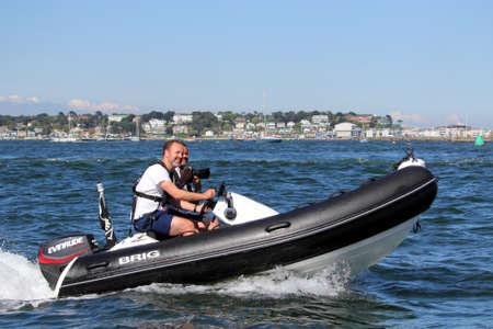 Poole, Dorset, England - June 02 2018: Two caucasian men driving fast through Poole Harbour on a rigid inflatable dinghy or RIB, one with a Canon camera,  luxury Sandbanks housing in background