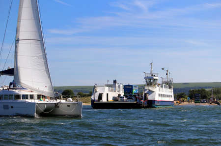 Sandbanks, Dorset, England - June 02 2018: A sailing catamaran passes the Sandbanks Chain Ferry which crosses the entrance of Poole Harbour Editoriali