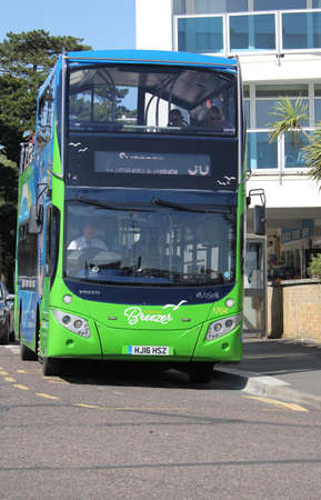 Sandbanks, Dorset, England - June 02 2018: The Purbeck Breezer Double decker open top bus waiting to board the Sandbanks Chain Ferry which crosses the entrance of Poole Harbour