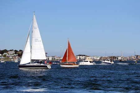 Sandbanks, Dorset, England - June 02 2018: Two sailing boats, and two motor boats, sailing through Poole Harbour in line, on a clear sunny summer day, with the luxury Sandbanks houses in the distance Sajtókép