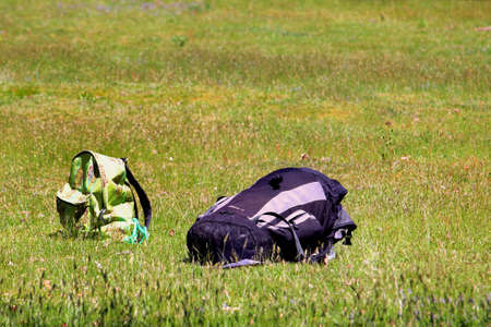 Brownsea, Dorset, England - June 02 2018: Two rucksacks, one large black and grey, one small green and patterned, in a grass meadow in summer sunshine