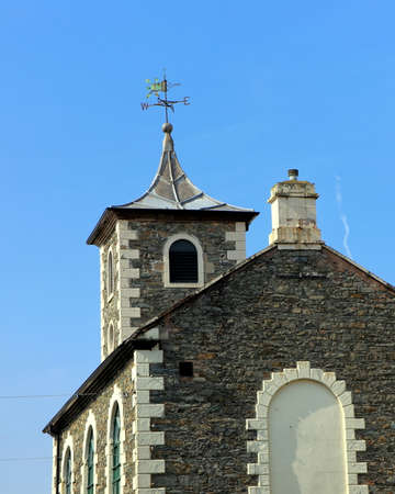 Old rustic stone church or chapel exterior with weather vane