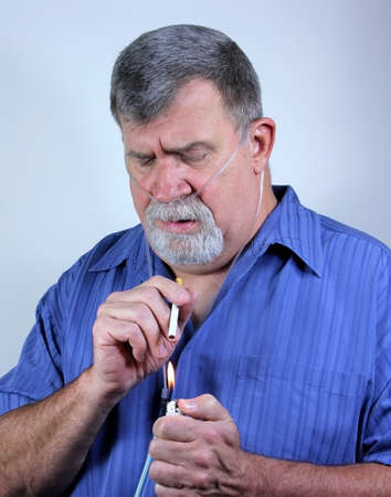 A man on COPD oxygen therapy dangerously lights a cigarette photo