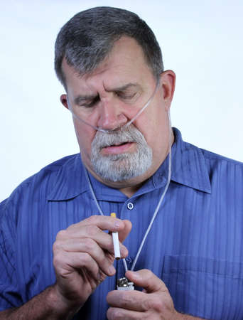 A man on COPD oxygen therapy attempts to light a cigarette photo