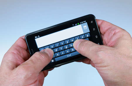 texting: Texting Thumbs op Smartphone Stockfoto
