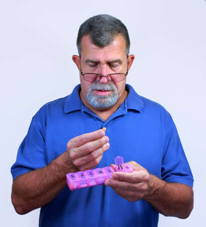 Senior Adult Male with Daily Pill Dispenser Stock Photo