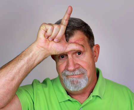 Adult Man with the Derogatory 'L for Loser' Hand Sign on Forehead photo