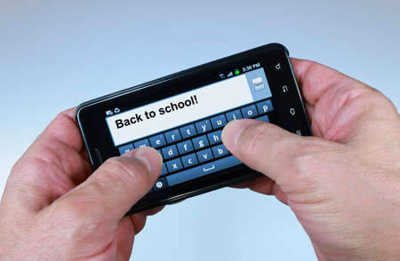 Thumbs texting Back to school on a smartphone photo