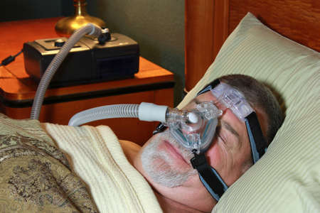 Senior Man Sleeps with CPAP photo