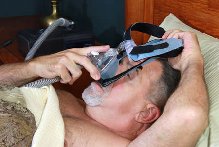 Adult Man Adjusting CPAP Mark Heargear Stock Photo - 17424992