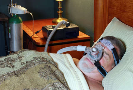Adult Man sleeping Peacefully with CPAP and Oxygen Stock Photo