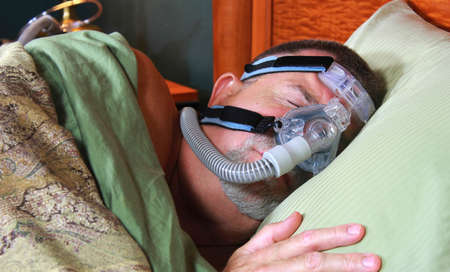 restful: Adult Man Sleeping Peacefully with CPAP Mask