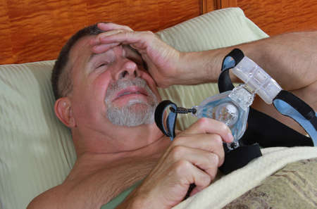 expressing: Adult Man Frustrated with CPAP Mask Stock Photo
