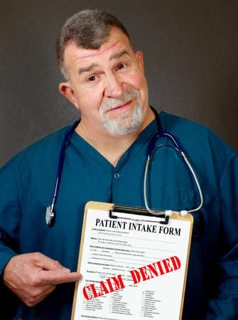 tilted: Doctor Points to Clipboard with CLAIM DENIED Stamped on it Stock Photo