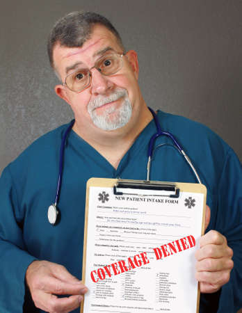 Doctor Displays Patient Intake Form with COVERAGE DENIED Stamped on it