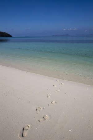footprints walking into aqua waters photo