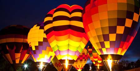 Eine Reihe von Hot Air Balloons feuern ihre Brennern Aufleuchten den gesamten Ballon. Carolinas Balloon Festival, Statesville, North Carolina.
