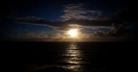 A full moon rises over the Pacific Ocean off the coast of Oahu, Hawaii