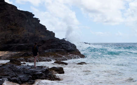 blow hole: A young woman watches the Halona Blow Hole on the shore of Oahu, Hawaii  Stock Photo
