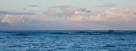 waikiki beach: A single sailboat sits at anchor in the Pacific Ocean just off of Waikiki Beach, Hawaii