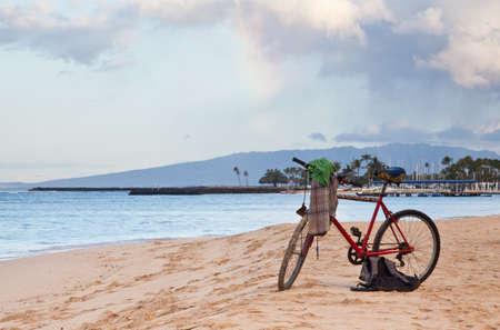 waikiki beach: A man ditches his shirt and bicycle on the beach and goes for a swim  Waikiki Beach, Hawaii