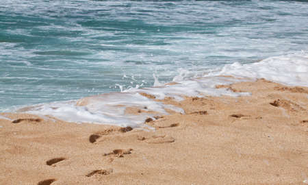 Footprints in the sand with surf and Ocean  Oahu, Hawaii photo