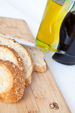 Multigrain bread with a bread knife and cutting board and bottles of vinegar and oil  photo