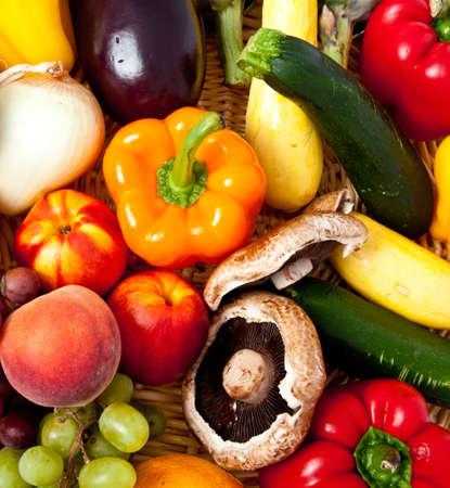 Een aantal verse groenten en fruit in een rieten mand op een witte achtergrond