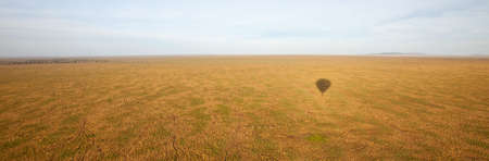 The Shadow of a Hot Air Balloon apears on the sweaping landscape of the Serengeti. Tanzania