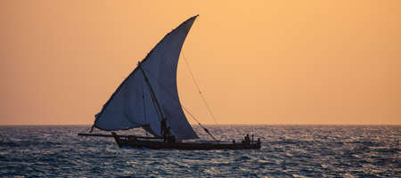 Fishermen sail their dhow into the sunset off the coast Zanzibar, Tanzania. photo