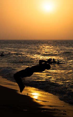BACKFLIP: A Zanzibari teanager does a backflip into the surf. Silhouetted by a setting sun. Zanzibar, Tanzania Stock Photo