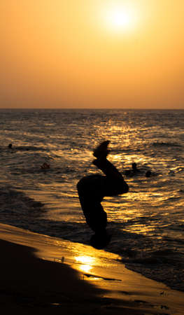 backflip: A Zanzibari teanager does a backflip into the surf. Silhouetted by a setting sun. Zanzibar, Tanzania Stock Photo