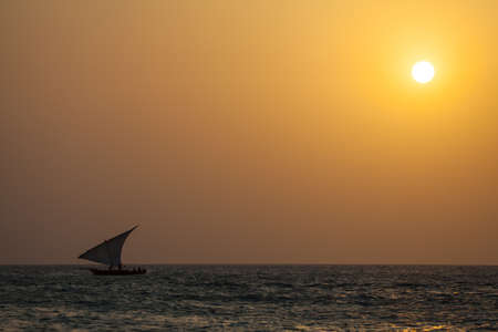 A group of local fishermen head out for the evening's work in their dhow. Zanzibar, Tanzania photo
