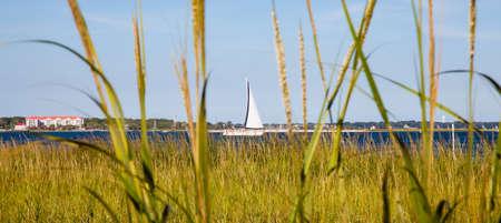 carolina del sur: Un barco de vela se abre paso por el r�o cooper como se ve desde las ca�as de Charleston, Carolina del Sur Foto de archivo