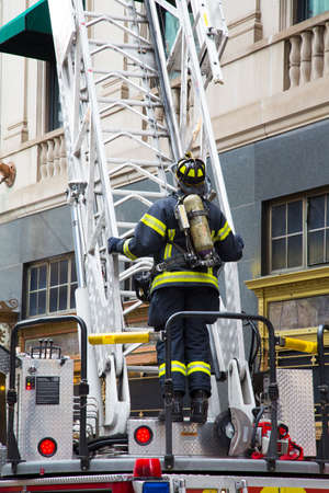 first responder: A fireman stands ready to climb the latter on the back of a firetruck at a hotel fire alarm in Boston, Massachusetts
