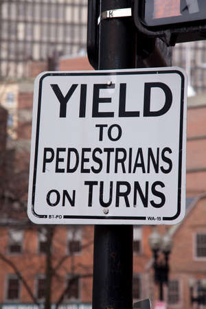 requiring: A sign in Boston requiring a yield to pedestrians on turns.