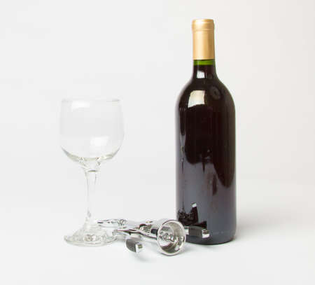 cork   screw: A bottle of Red wine, empty wine glass, and a cork screw on a white background.