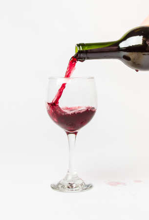 Red Wine pouring out of a bottle into a glass and splattering the white background. photo