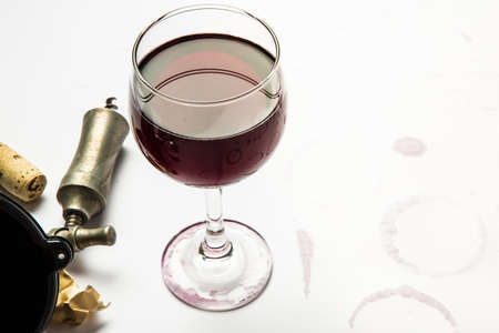 A full glass of red wine with wrapper, cork, and cork screw with wine ring stains from the glass. Stock Photo - 19604112