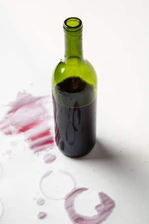 Red wine bottle, partially empty with wine stains around it.