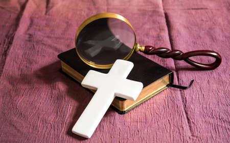 A bible, cross and magnifying glass. The cross is reflected in the glass of the magnifying glass.