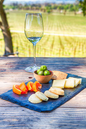 A glass of wine with fruit, cookies, cheese, and crackers. A traditional wine tasting at a Sonoma County Vineyard. Stock Photo