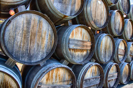 Rustic oak wine barrels stacked at a California winery.