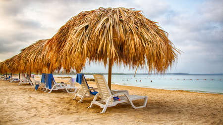 beach front: Lounge chairs under thatch umbellas on the white sand of a Caribbean beach front resort. Stock Photo