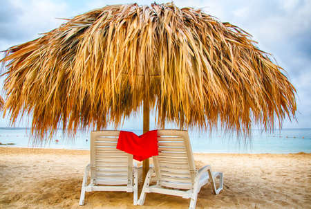 lounge chairs: Lounge chairs under thatch umbellas on the white sand of a Caribbean beach front resort. Stock Photo