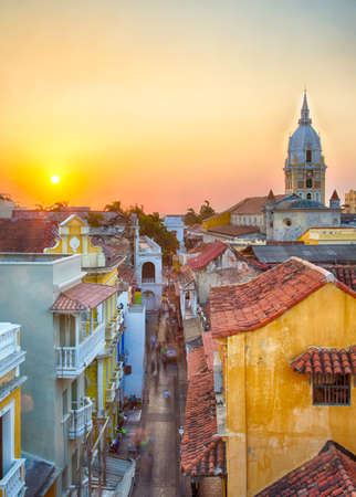 cartagena: View over the rooftops of the old city of Cartagena during a vibrant sunset. The spire of Cartagena Cathedral stands tall and proud.