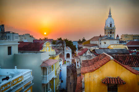 rooftop: View over the rooftops of the old city of Cartagena during a vibrant sunset. The spire of Cartagena Cathedral stands tall and proud.